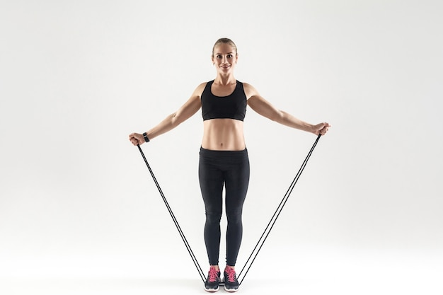 Treinamento trx. mulher de felicidade atividade segurando corda de pular, sorrindo e olhando para a câmera. foto do estúdio, fundo cinza