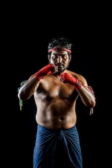 Treinamentos tailandeses do homem do pugilista de muai. estúdio filmado em preto