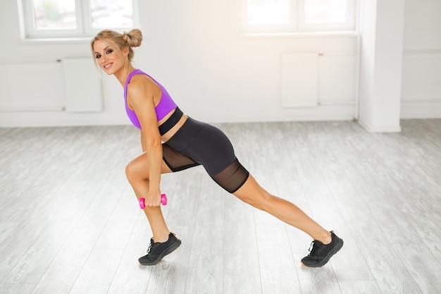 Treinando mulher jovem e bonita no ginásio com halteres