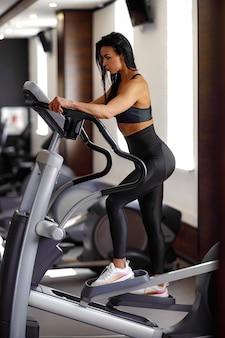 Treinando na academia fitness girl coach trabalhando na máquina de step