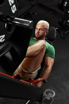 Treinando pernas no simulador, o atleta trabalha com as pernas no simulador, trabalhando os músculos das pernas.