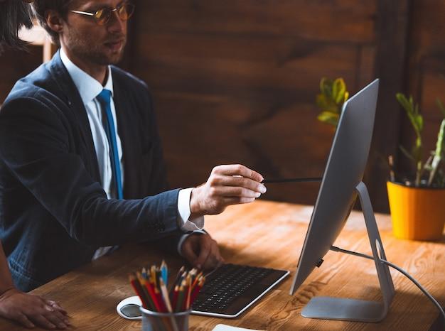 Treinar a equipe do escritório para o empresário do plano de marketing comercial mostrando o projeto atualizado aos funcionários sentados no escritório