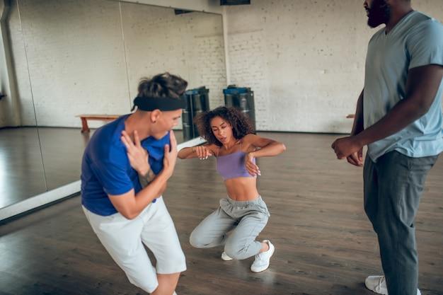 Treinar, dançar. jovem envolveu garotos e garotas em roupas confortáveis e tênis dançando vigorosamente no ensaio