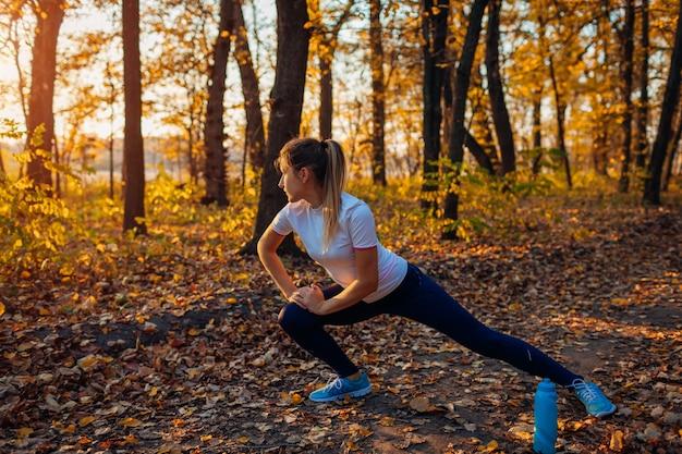 Treinar e exercitar-se no parque outono, mulher esticando as pernas ao ar livre, estilo de vida saudável e ativo