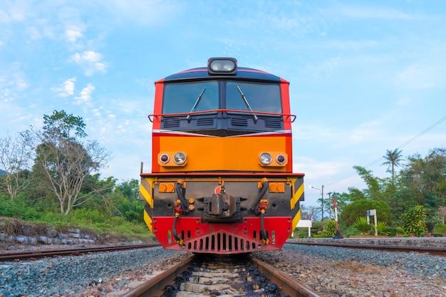 Treine locomotivas elétricas diesel nas trilhas na estação de tailândia com céu azul.