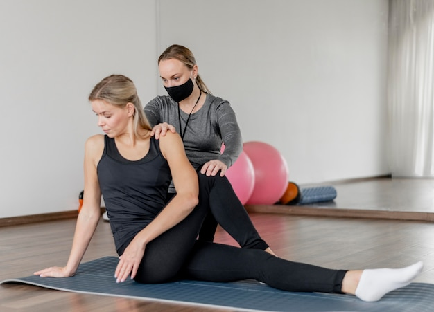 Treino com personal trainer usando máscara preta