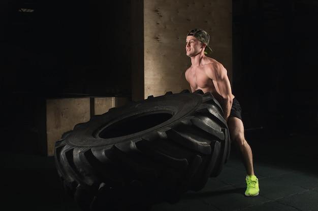 Treino crossfit. homem lançando pneu