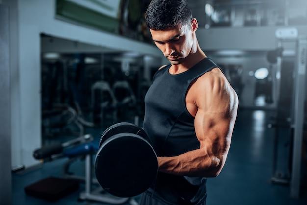 Treino de atleta musculoso bronzeado com halteres no ginásio.