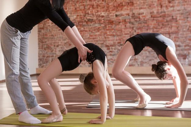 Treino de bailarinas. vida de esporte adolescente. ginástica rítmica de meninas em foco em primeiro plano com a treinadora. plano de fundo do ginásio, estilo de vida adolescente saudável, conceito de exercício
