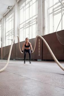 Treino de corda de batalha. jovem, magra, caucasiana, vestindo roupas esportivas pretas, queimando calorias fazendo exercícios com cordas na academia