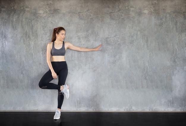 Treino de exercício de mulher no ginásio, atleta construtor músculos estilo de vida. aptidão quebrar relaxar segurando a fruta da maçã após o esporte de treinamento com haltere e proteína shake garrafa estilo de vida saudável