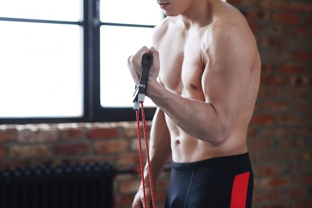 Treino de fitness homem. homem sem camisa, fazendo alongamento em casa