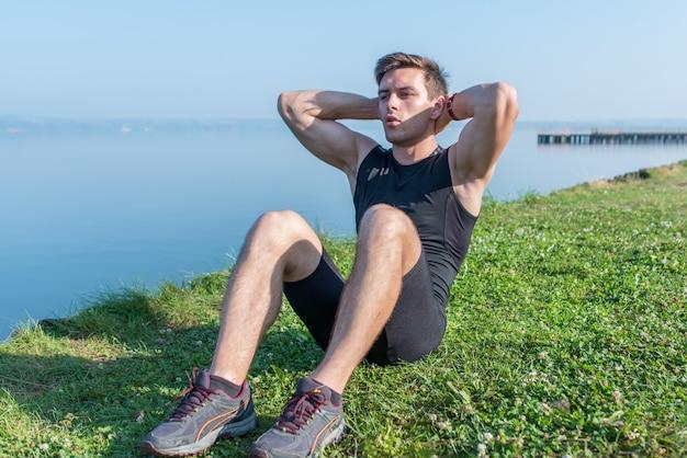 Treino de fitness. jovem desportista fazendo abdominais ao ar livre.
