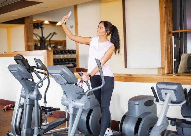 Treino de garota fitness no ginásio. exercícios para mulheres, trem fisiculturista, estilo de vida esportivo