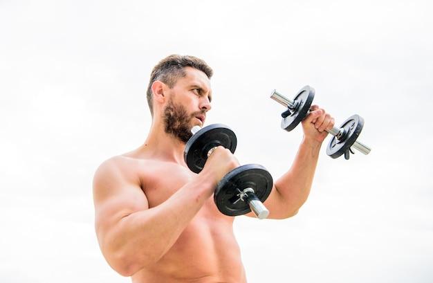 Treino de ginásio. esporte de fitness de treino. conceito de treino. mente saudável em um corpo são. homem musculoso, exercitando-se com halteres. exercício com halteres. ouse ser grande. esportista bíceps tríceps forte.