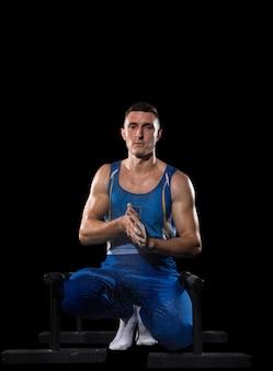 Treino de ginasta masculino musculoso em ginásio, flexível e ativo.