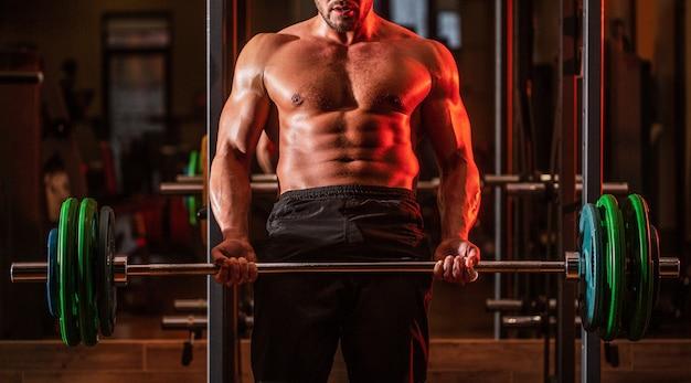 Treino de halteres treino de homem musculoso com barra na academia fisiculturista homem atlético com tanquinho