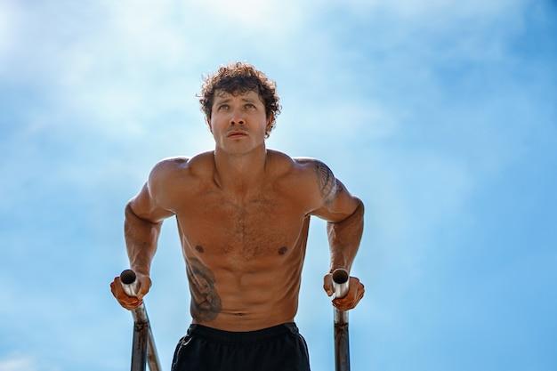 Treino de homem apto para fora braços em barras horizontais mergulhos, treinamento de tríceps e bíceps fazendo flexões bonito ...