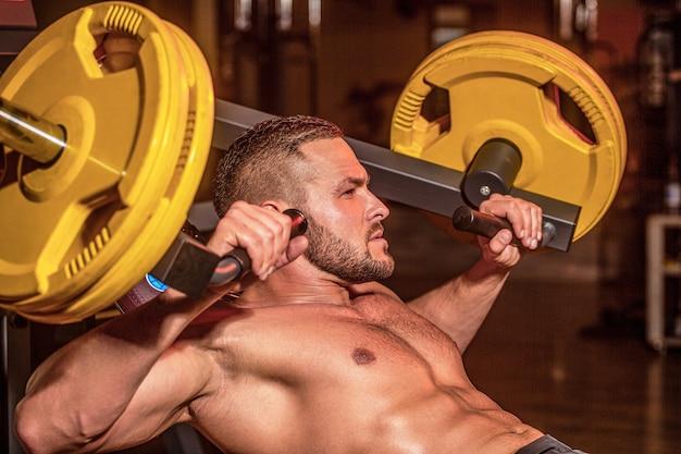 Treino de homem musculoso com peso no ginásio. homem atlético fisiculturista com tanquinho, abdômen perfeito, ombros, bíceps, tríceps, peito. treino de halteres. cara atlético em pé com barra, treino no ginásio.