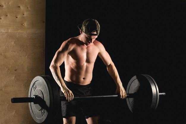 Treino de homem no ginásio fazendo exercícios com barra