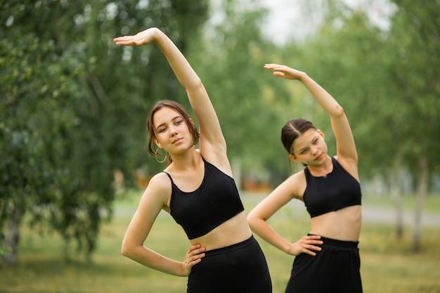 Treino de ioga de rua de duas mulheres no parque