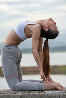 Treino de ioga, jovem mulher fazendo exercícios de ioga na parede em belos lagos de montanha