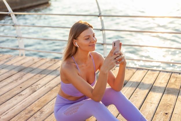 Treino de manhã. mulher jovem esporte sportswear usa smartphone enquanto está sentado na praia ao nascer do sol