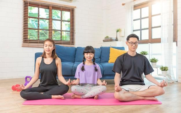Treino de meditação saudável de família asiática em casa, exercício, ajuste, fazendo ioga. conceito de fitness de esporte doméstico