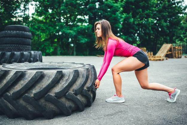 Treino de menina muito desportivo ao ar livre com grande pneu