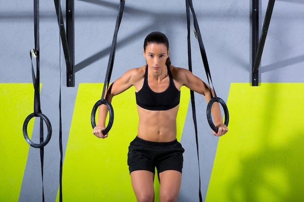 Treino de mulher de anel de mergulho crossfit no ginásio mergulhando