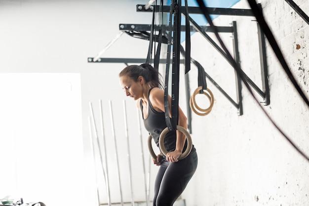 Treino de mulher de anel de mergulho fitness no ginásio mergulhando exercício