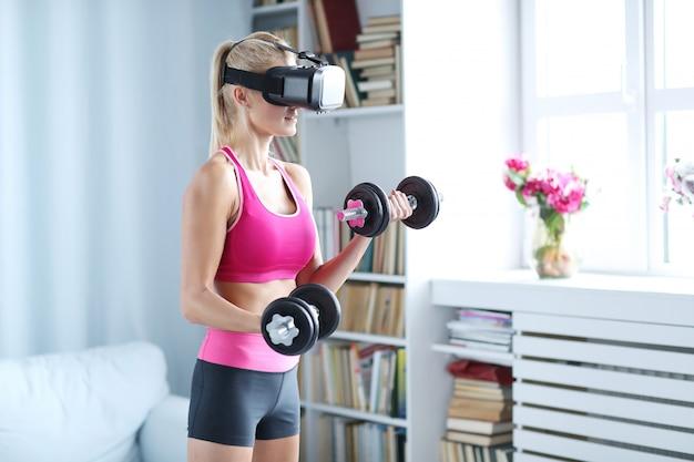 Treino de mulher fitness com halteres e fone de ouvido vr