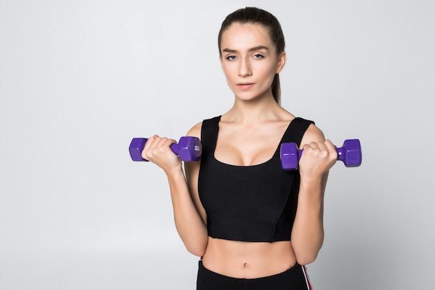Treino de mulher sorridente fitness com halteres pequenos isolados em uma parede branca
