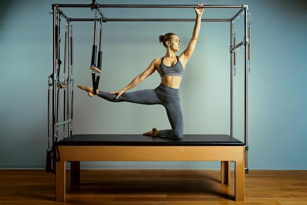 Treino de pilates de treino de malha. exercícios de reformador de pilates atléticos. equipamento da máquina de pilates.