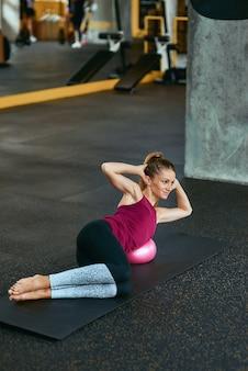 Treino de pilates. jovem mulher caucasiana em roupas esportivas, deitada no tapete de ioga na academia e fazendo exercícios abdominais, usando uma pequena bola de fitness. esporte, treino, bem-estar e estilo de vida saudável
