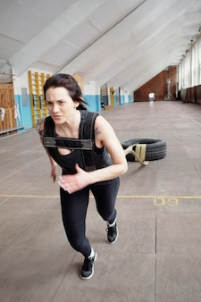 Treino de puxar o pneu. jovem atractiva desportista caucasiana a arrastar o pneu com cordas durante o treino transversal no pavilhão desportivo
