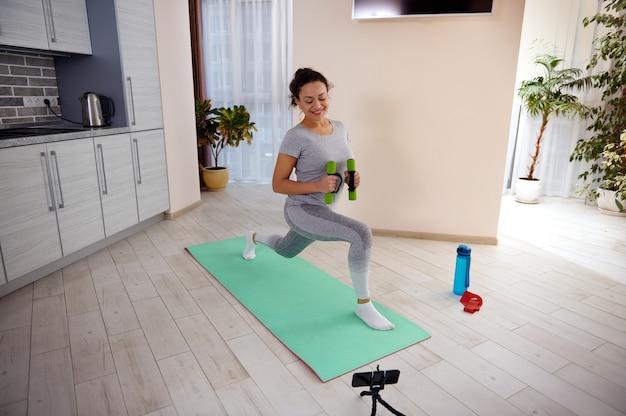 Treino de uma mulher fitness fazendo exercícios de estocagem para os músculos das pernas enquanto assiste a tutoriais em casa