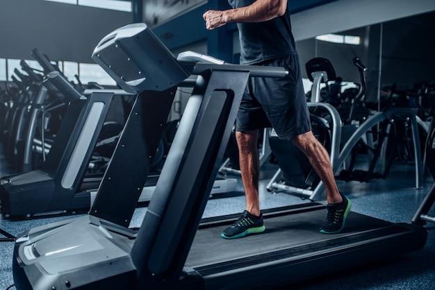 Treino do indivíduo do sexo masculino na máquina de exercícios em execução. treinamento esportivo ativo na academia