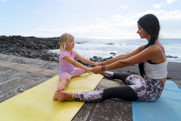 Treino em família. jovem desportiva mãe e filha com roupas de esporte, exercitando-se juntos, alongando-se no tapete, olhando um para o outro e sorrindo. conceito de estilo de vida saudável