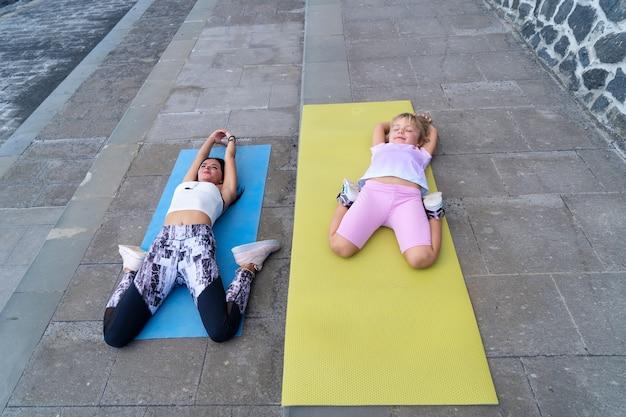 Treino em família. jovem desportiva mãe e filha com roupas de esporte, exercitando-se juntos, estendendo-se na esteira. conceito de estilo de vida saudável