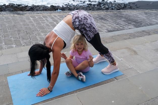 Treino em família. jovem desportiva mãe e filha com roupas de esporte, exercitando-se juntos, estendendo-se no tapete de ioga. conceito de estilo de vida saudável