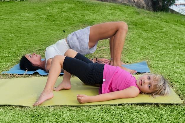 Treino em família. jovem desportiva mãe e filha com roupas de esporte, exercitando-se juntos na grama verde, estendendo-se no tapete de ioga. conceito de estilo de vida saudável