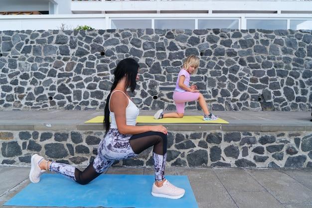Treino em família. jovem desportiva mãe e filha em roupas esportivas, exercitando-se juntos, alongando-se e equilibrando-se no tapete.