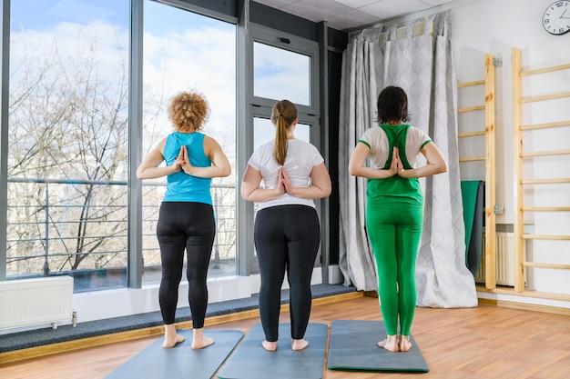 Treino em grupo, treino, ioga, fitness, exercícios de três mulheres, ficar para trás com as mãos em namaste