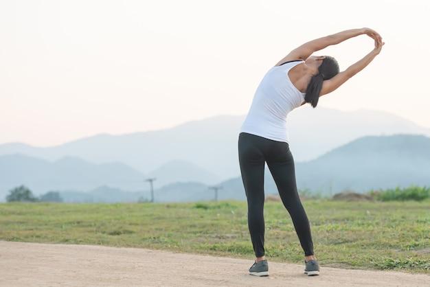 Treino feminino jovem antes da sessão de treinamento de fitness no parque.