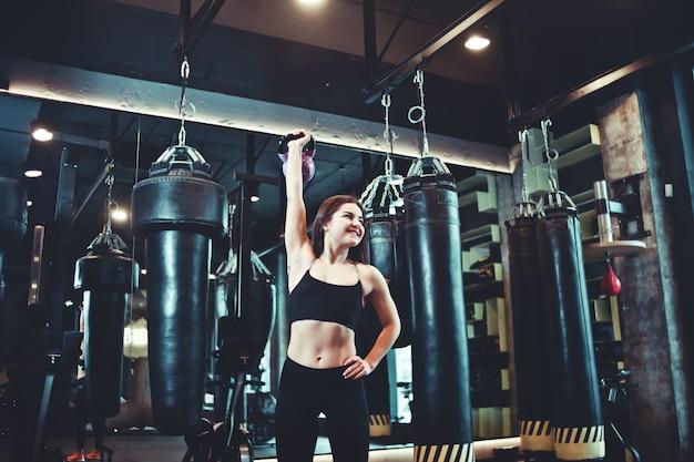 Treino funcional. mulher de aptidão fazendo exercícios com kettlebell.