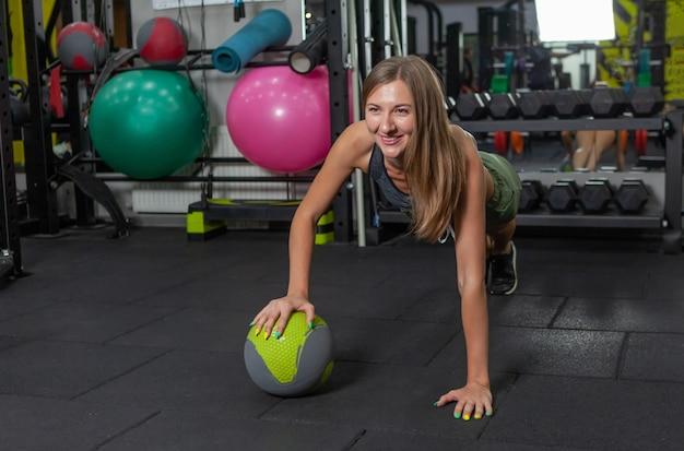 Treino funcional. musculação e fitness. jovem mulher alegre fazendo flexões com bola medicinal em uma academia moderna