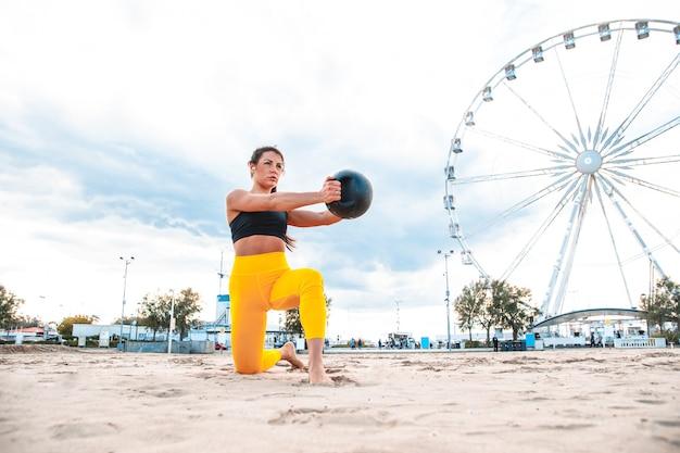 Treino funcional na praia, mulher em forma e atlética praticando esportes ao ar livre