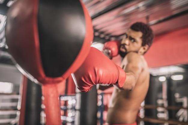 Treino. kickboxer afro-americano se exercitando em uma academia e parecendo concentrado