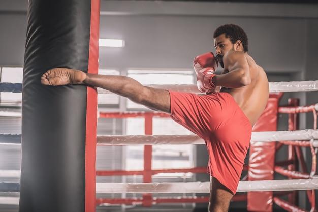 Treino. kickboxer jovem de pele escura chutando um saco de areia com a perna